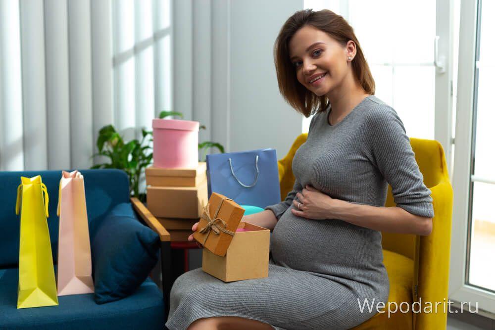 вагітна жінка відкриває подарунки