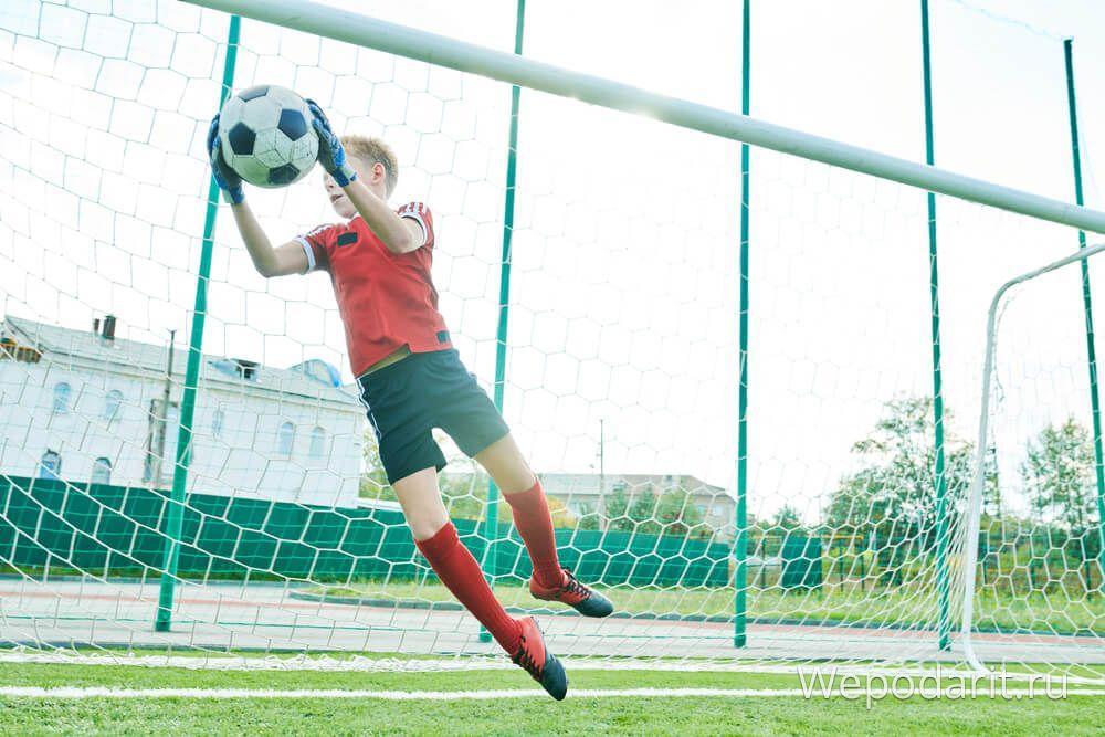 хлопчик-воротар ловить м'яч