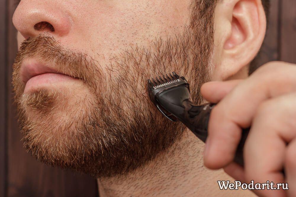 чоловік використовує триммер для бороди
