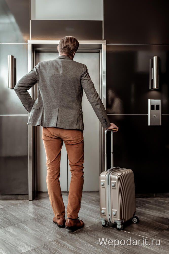 чоловік в піджаку з дорожнім валізою
